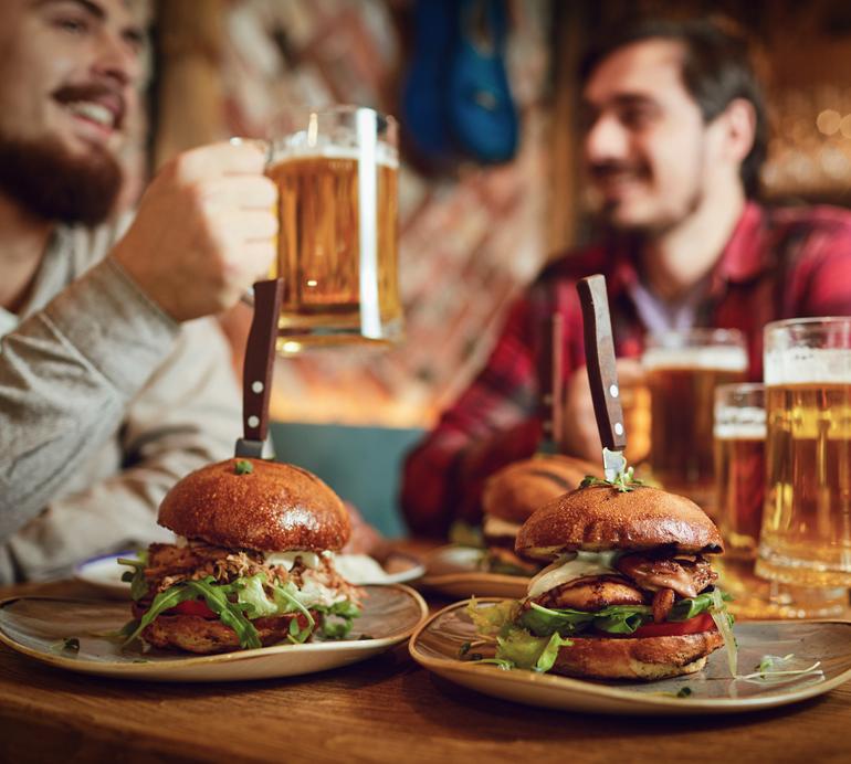 group of guys enjoying burgers and beer at saints pub at lenexa citycenter