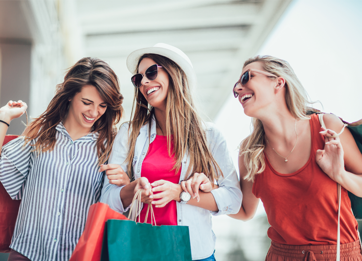 three girlfriends talking and laughing while walking outside with shopping bags