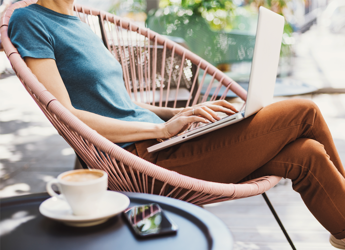 young woman working on laptop outside with espresso drink